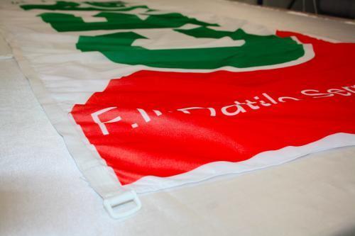 Dettaglio tela di rinforzo e D-ring in plastica per tendi peso bandiere.